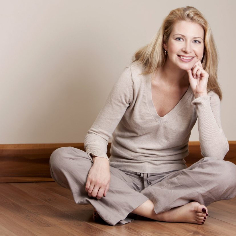 15814949 - pretty blond woman wearing beige top relaxing on the floor