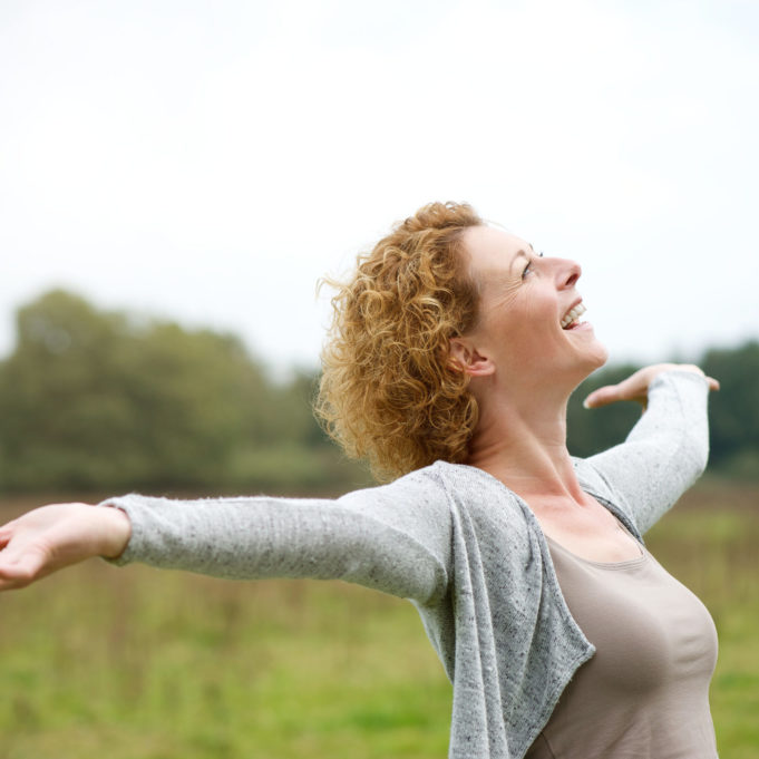 31616441 - close up portrait of a cheerful carefree woman with arms outstretched