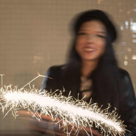 71376922 - blurred shot of young woman having fun with sparkler in her hands in night city, light painting, retro color, defocused image